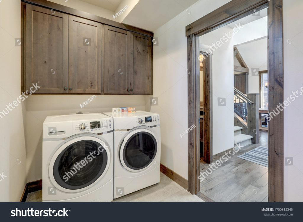 stock-photo-laundry-room-with-white-wahser-and-dryer-and-dark-brown-wood-cabinets-1700812345
